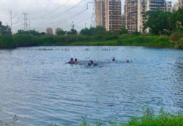 Adults and children using tyres to swim at Taloja Jail pond